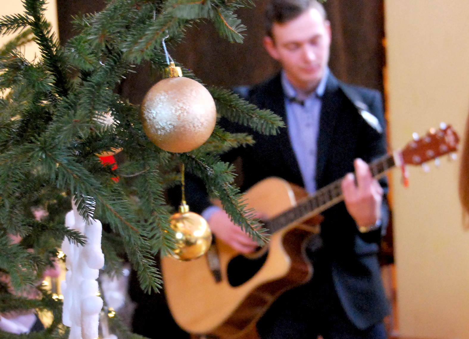 zdjęcie przedstawia pana grającego na gitarze i choinkę bożonarodzeniową na pierwszym planie
