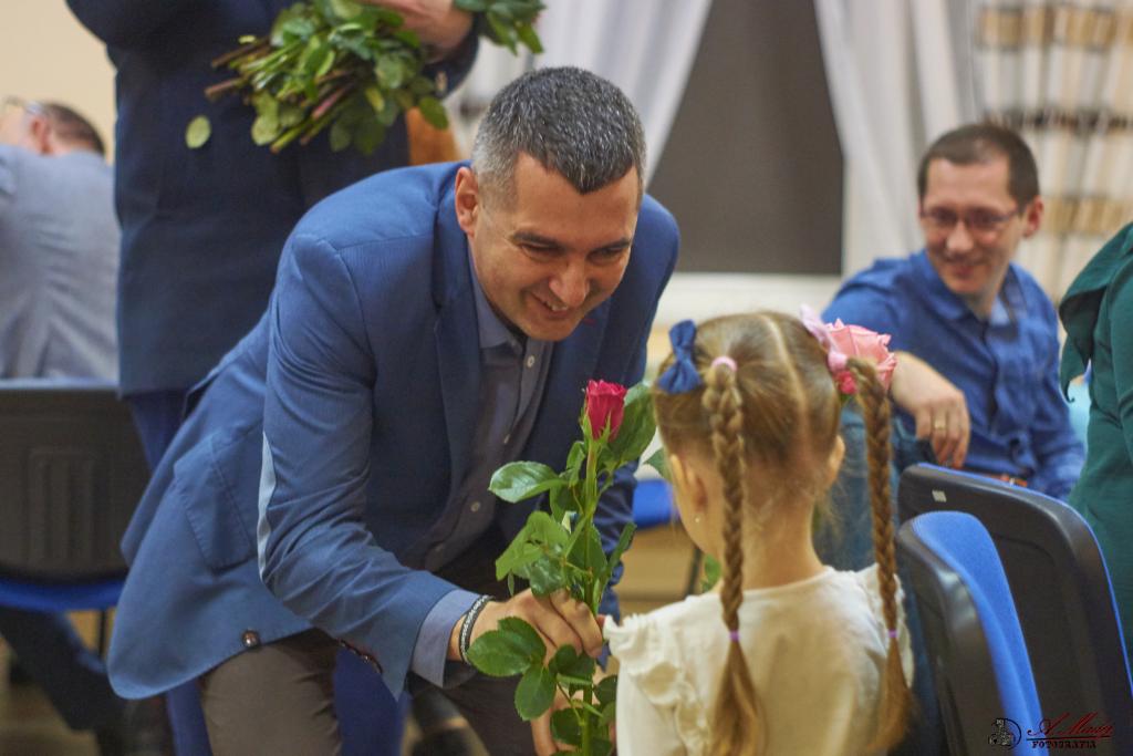 zdjęcie przedstawia wójta rafała plezie wręczającego różę dziewczynce