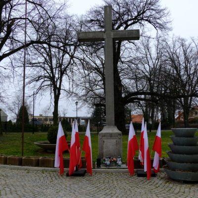 Zdjęcie przedstawiające krzyż i flagi polskie