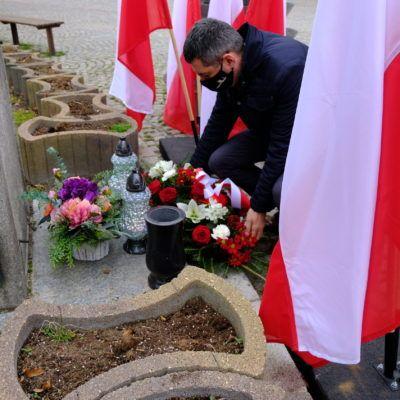 zadjęcie przedstawiające Wójta Rafała Plezię składającego kwiaty pod krzyżem