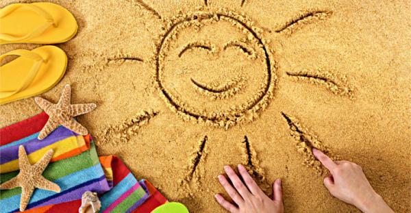 zdjęcie przedstawia piasek, słońce, ręcznik i klapki plażowe